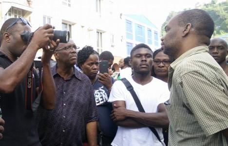 Local media interviewing Grenadian journalist Hamlet Mark (R) following his release without charge after he was arrested by police in St Vincent while reporting on a public protest. Photo: NDP/Facebook